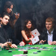 Stylish woman in black suit folds two cards in casino poker at Las Vegas ov - Stock Photo
