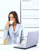 Happy young woman filling a business form while on her desk at work — Stockfoto