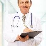feliz sorrindo doutor maduro escrevendo na área de transferência em um hospital moderno — Foto Stock