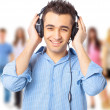 Portrait of a happy young guy listning to music against white background - Stock Photo