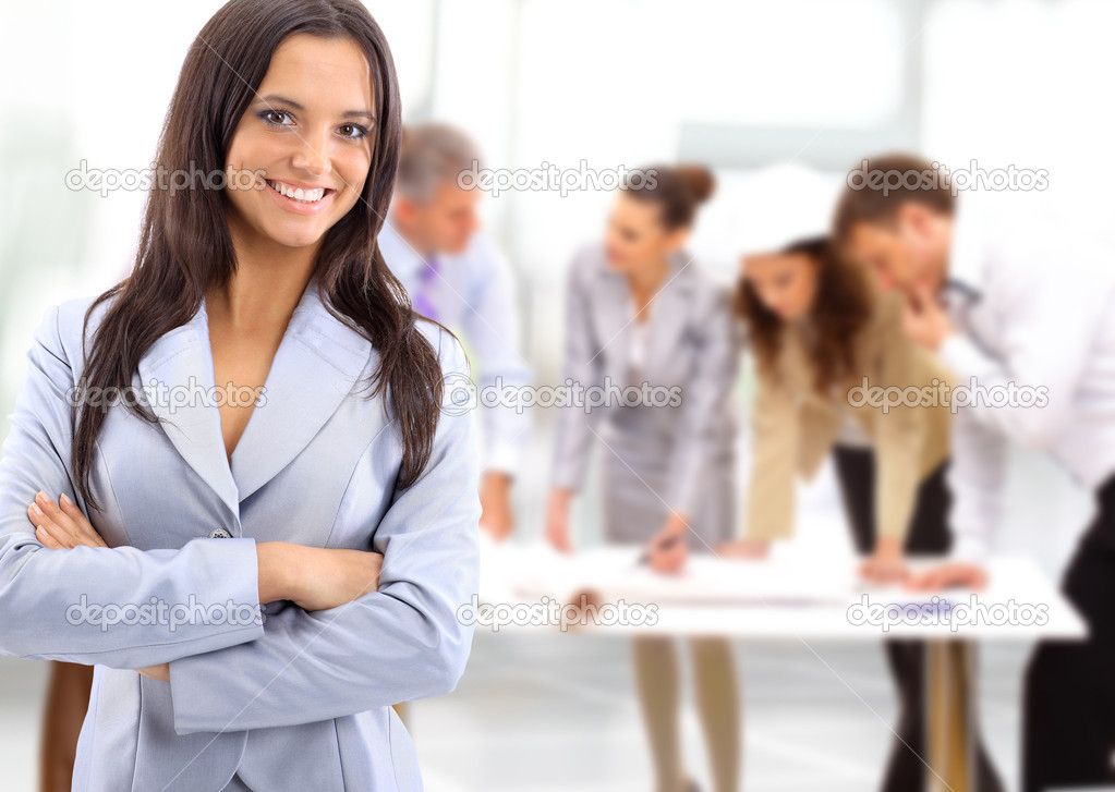 Portrait of a charismatic woman at a meeting while her team working in the background   Stock Photo #5260802