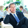 Business man speaking on the phone while in a meeting — Stock Photo