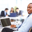 Portrait of a happy African American entrepreneur displaying computer lapto — Foto Stock