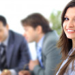 A confident relaxed business woman smiling with her colleagues at the back — Stock Photo