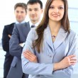 Royalty-Free Stock Photo: Young business woman with her team in the background.