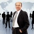 Businessman standing in front of an earth map — Stock Photo