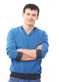 Portait of a handsome young man standing with his hands in pocket against w — Stock Photo