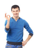 Portrait of a smiling handsome young man gesturing ok sign against white ba — Stock Photo