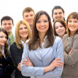 Happy young business woman standing in front of her team — Stock Photo #5351070