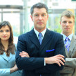 Foto de Stock  : Confident mature business man with colleagues at the background