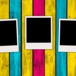 Three Blank Photos on Multicolored Wood Background — Stock Photo