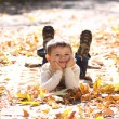 Child lying on the golden leaf - Foto Stock