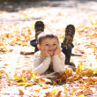 Child lying on the golden leaf - Stockfoto