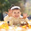 Child lying on the golden leaf — Stock Photo #4084313