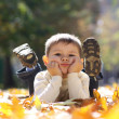 Child lying on the golden leaf — Stock Photo #4084330