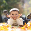 Child lying on the golden leaf — Stock Photo #4084340
