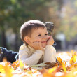 Child lying on the golden leaf — Stock Photo #4084359