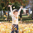 Child lying on the golden leaf — Stock Photo #4084445