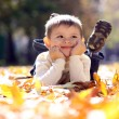 Child lying on the golden leaf — Stock Photo #4084687