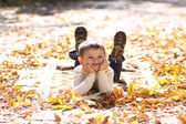 Child lying on the golden leaf — Stok fotoğraf