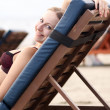 Stock Photo: Woman sunbathes lying on chaise lounges