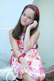 Little girl talks by mobile phone — Stock Photo