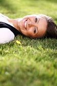 Söt ung kvinna liggande på gräsplan på park — Stockfoto