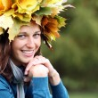 Beautiful woman with diadem made from yellow maple leaves - Stok fotoğraf