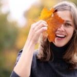 Beautiful romantic brunette with golden autumn leaf — Stock Photo