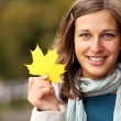 Beautiful romantic brunette with golden autumn leaf — Stock Photo