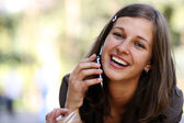 Happy young lady talking on mobile phone — Stockfoto
