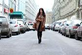 Beautiful young woman walking on the street — Stock Photo