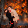 Young happy couple in autumn park — Stock Photo