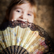 Girl covering her face with a lacy fan — Stock Photo