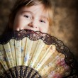 Stock Photo: Girl covering her face with a lacy fan