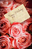 A bouquet of pink roses with a greeting card — Stock Photo
