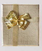Holidays background of golden box with ribbon — Stok fotoğraf