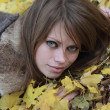 Stock Photo: Girl lies on maple leaves