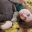 Stock Photo: Young girl lying on maple leaves