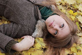 Young girl lying on maple leaves — Stock Photo