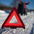 Man And Woman Broken Down On Country Road With Hazard Warning Sign In Foreg - Stock Photo