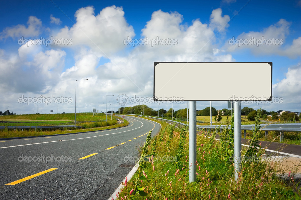 Road with sign pole and blue sky with clouds — Stock Photo #3957225