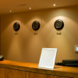 Reception desk with phone and row of clock — Stock Photo #4503099