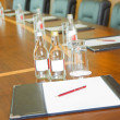 Table with  block-notes and bottles of water — Stockfoto
