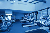 Row of jogging simulators in gym, monochromatic — Stock Photo