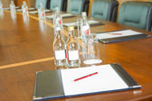 Table with block-notes and bottles of water — Stock Photo