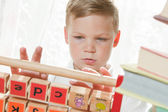 Boy put together letters — Stock Photo