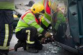 Fireman with Power Wedge at car crash — Stock Photo