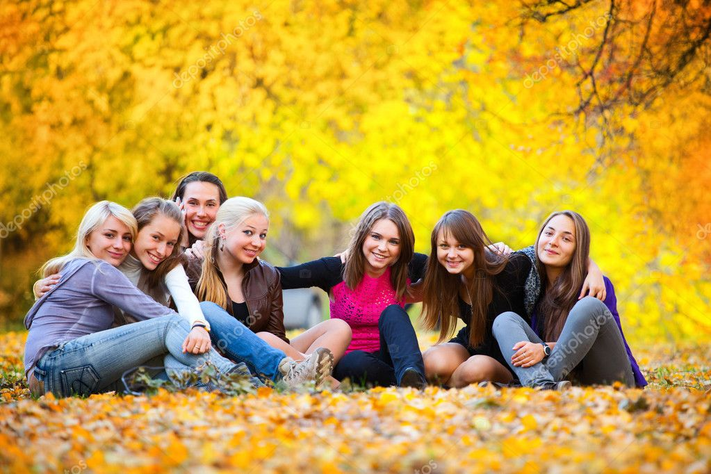 Many young girls in the autumn park sitting on the grass — Stock Photo #3942833