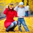 Child and mother with autumn leaves — Stock Photo #4013041